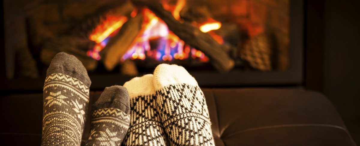Close up couple's socks in front of a fireplace.