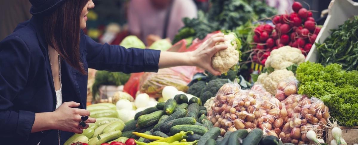 Woman grabbing cauliflower.