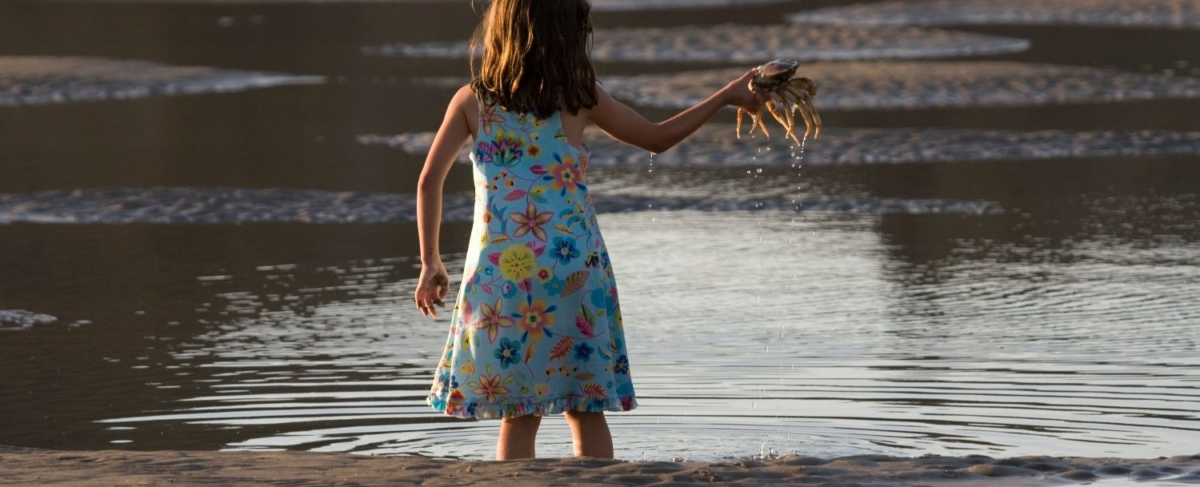Young girl holding a crab.