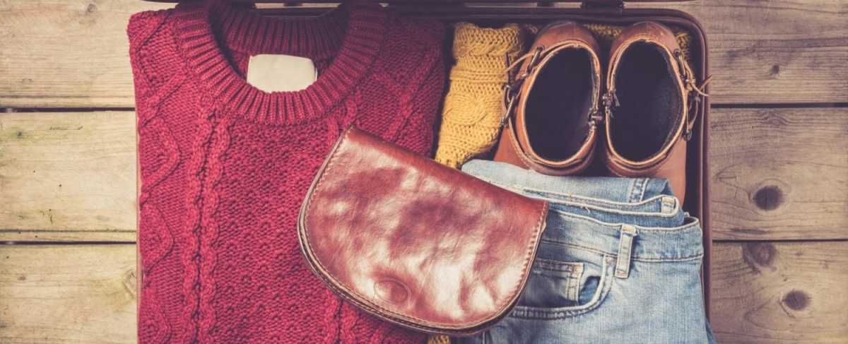 Winter suitcase packed with sweater and jeans.