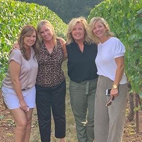 Four women posing in a vineyard field.