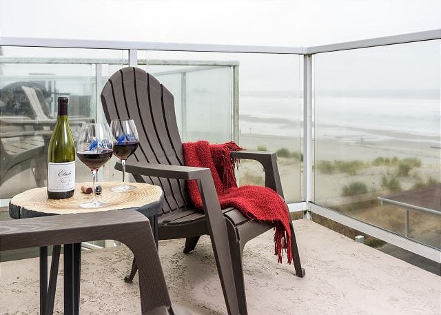chair on balcony with wine and blanket