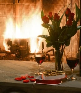 roses, wine, and chocolates in front of lit fireplace