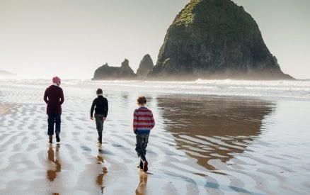 Family walking on Oregon coast beach.