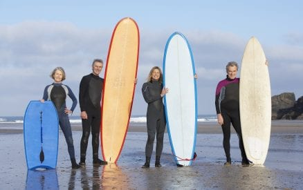 Four adults on the beach with surfboards and a boogie board