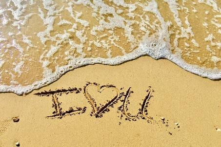 """Photo of """"I love you"""" carved into the beach sand."""